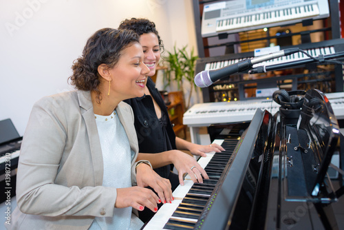 Poster Women playing duet on piano and singing