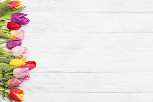 colorful tulips on white wooden background.