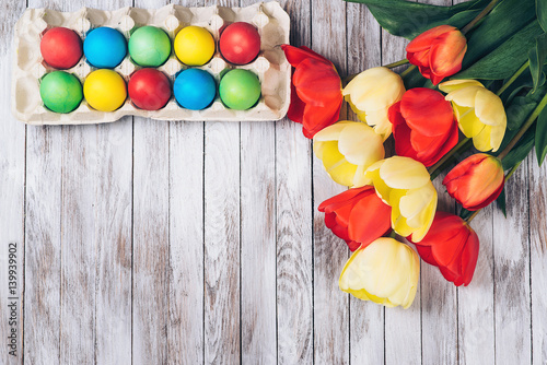 Colored easter eggs and fresh tulips on white wooden background.
