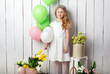 Cheerful little blonde girl with balloons on white wood background