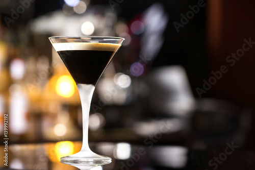 Glass of black russian cocktail at bar counter background. Poster
