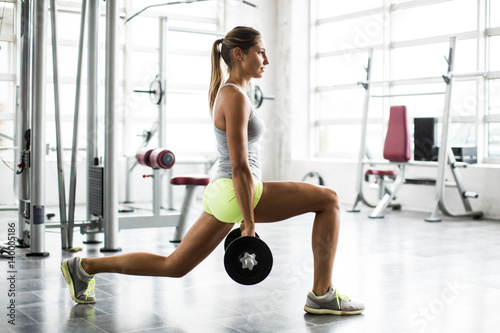 Focused young beautiful woman lifting weights in a gym