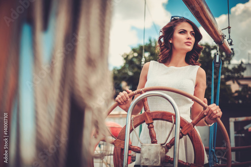 Poster Stylish wealthy woman on a luxury wooden regatta