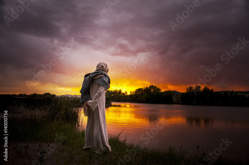 Jesus Christ overlooking a sun setting on the lake Poster