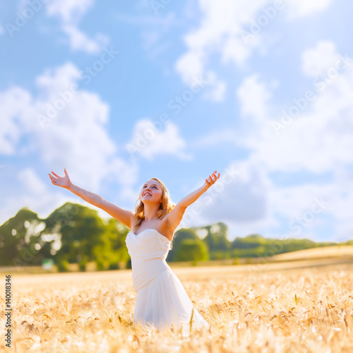 Beautiful girl in white dress at wheat field