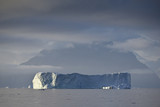 huge iceberg in front of misty landscape