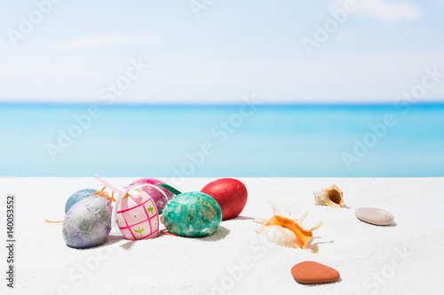 Easter on tropical beach background. Eggs on the white sand. Vacation and travel concept