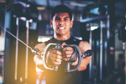 Handsome muscular man exercise with cable weight machine in gym. close up hand