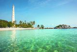 White lighthouse standing on an island in Belitung at daytime surrounded by clear blue green colored ocean water with no people around.