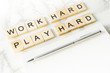 Work Hard Play Hard text on scrabble wood in office desk concept