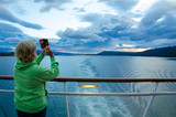 Cruise ship passenger photographs the sunrise with her smart phone. - 140102594