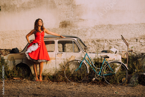 Poster Beautiful girl in red dress in a car workshop