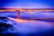 Golden Gate Bridge at dawn surrounded by fog from Marin Headlands in San Francisco, California