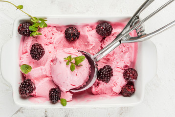 Homemade berry ice cream to the pan (bowl), with blackberries and mint leaves. On the white stone table, top close view copy space