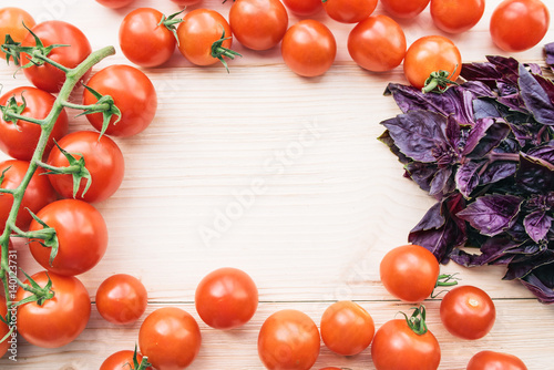 Ripe tomatoes and purple basil on a wooden table form frame for text inside. Tomatoes on a branch
