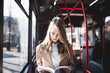 Beautiful young woman sitting in city bus and reading a book.