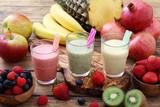 frappe' o frullato di frutta fresca tre bicchieri su sfondo rustico
