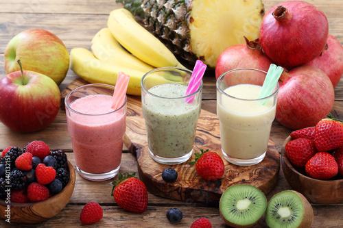 Poster Milkshake frappe' o frullato di frutta fresca tre bicchieri su sfondo rustico