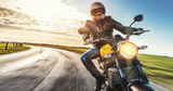 Motorrad fährt auf freier Landstrasse in den Sonnenuntergang - 140155348