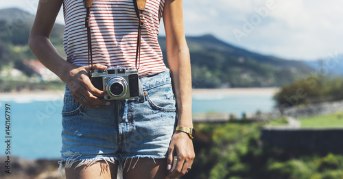 Tourist traveler photographer making pictures sea scape on vintage photo camera on background ocean, hipster girl enjoying peak mountain and nature holiday, mock up ocean waves view, blurred backdrop