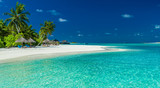 Fototapety Palm trees and beach umbrelllas over lagoon and white sandy beach, Maldives