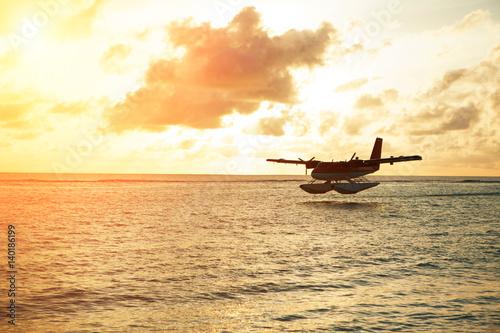 Foto op Aluminium Strand Summer sunrise with seaplane. Landing seaplane on the seashore. Calm scenery on morning sea.