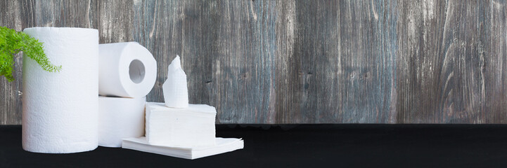 Paper tissue, paper towel and napkins on wooden background. Wide panoramic image.