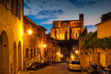 Night old street and view of San Domenico Cathedral in Siena, Tuscany, Italy.