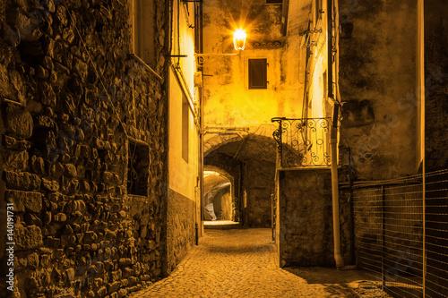 Ancient street with arch in the night in Santo Stefano di Magra, La Spezia, Italy.