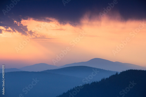 Fantastic sunrise above peaks of smoky mountain with the view into misty hills. Dramatic overcast sky. Mountains silhouettes.
