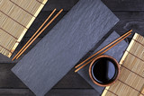 Background for sushi. Bamboo mat, soy sauce, chopsticks on dark table. Top view with copy space, for product display montage