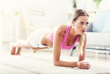 Fit girl in plank position at home in the living room - 140224356