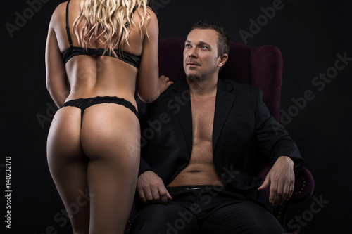 Sexy girl in underwear. Young man sitting on the chair. Black background - 140232178