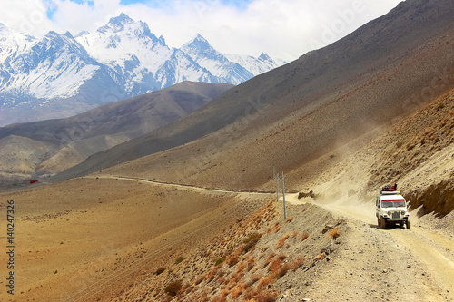 """A car with tourists on a mountain road in the Himalayan mountains. Nepal. The kingdom of """"Upper Mustang""""."""