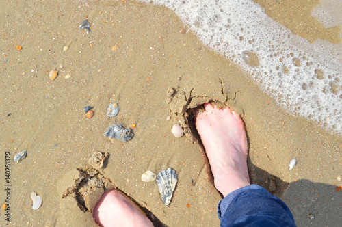 Bare feet on sandy shore Poster