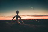 Omino seduto su un muro che immagina il futuro guardando il tramonto. - 140256552