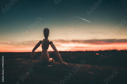 Omino seduto su un muro che immagina il futuro guardando il tramonto Poster