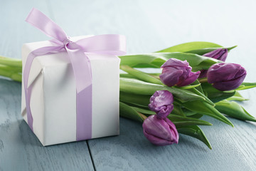 white gift box with purple bow and tulips on blue wood background, romantic photo