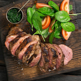Slices of steak grilled with salad of spinach leaves, tomatoes