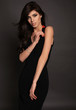 gorgeous woman with long dark hair posing in studio in black dress