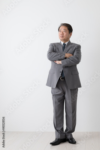 腕組みをするビジネスマン、中年男性
