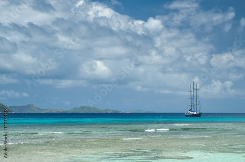 Lonely sailing ship next to amazing reef under turquoise-water