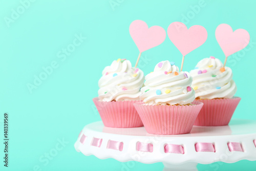 Tasty cupcakes on cake stand on green background