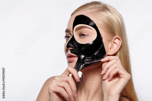 Poster Young attractive girl takes off black facial face