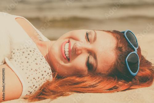 Redhead adult woman lying on beach