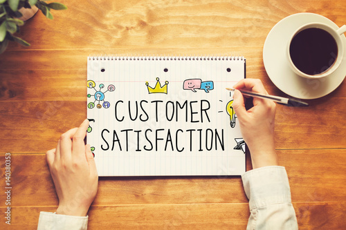 Customer Satisfaction text with a person holding a pen