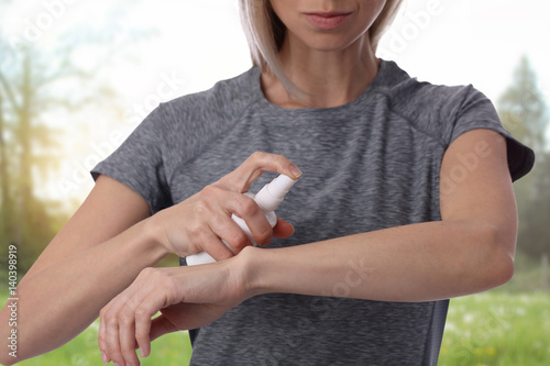 Woman spraying insect repellent on skin outdoor Poster