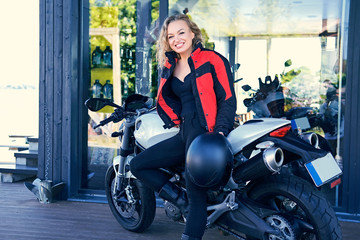 A woman posing with white speed motorcycle.