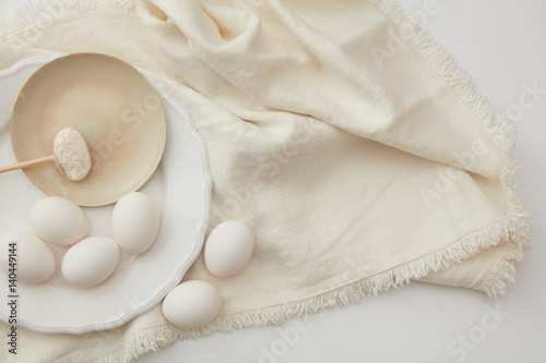 Raw eggs and spoon of flour