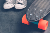 Skateboard and sneakers on a dark background